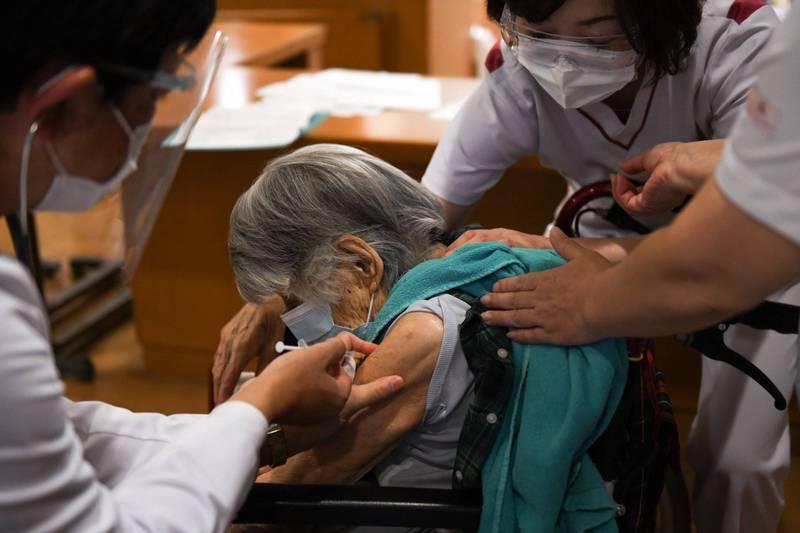 日本神戶市一家老人保健照護設施發生群聚感染,4月14日以來共有133人確診武漢肺炎,其中有25名入住者死亡,圖為醫師在為老人接種疫苗的畫面。(彭博)