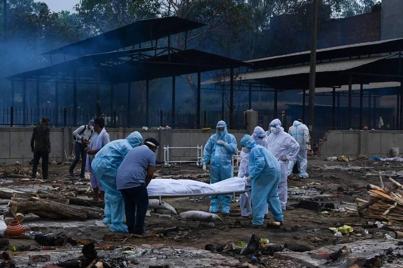 印度疫情仍持續惡化。圖為6日新德里民眾在墓地搬運武肺病逝親人。(法新社)