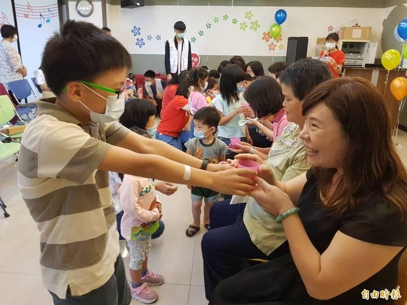 寄養媽媽對孩子視如己出的照顧,寄養孩童奉茶謝恩,祝媽媽「母親節快樂」。(記者游明金攝)