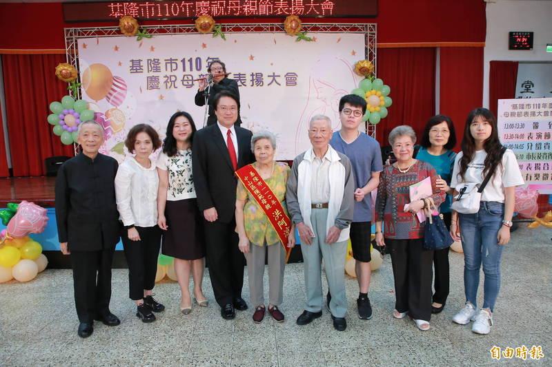 84歲洪阿涼育(前排左5)有2子5女,雖然學歷不高,卻非常重視子女的教育,夫妻倆熱心公益,受到街坊鄰居肯定。(記者林欣漢攝)