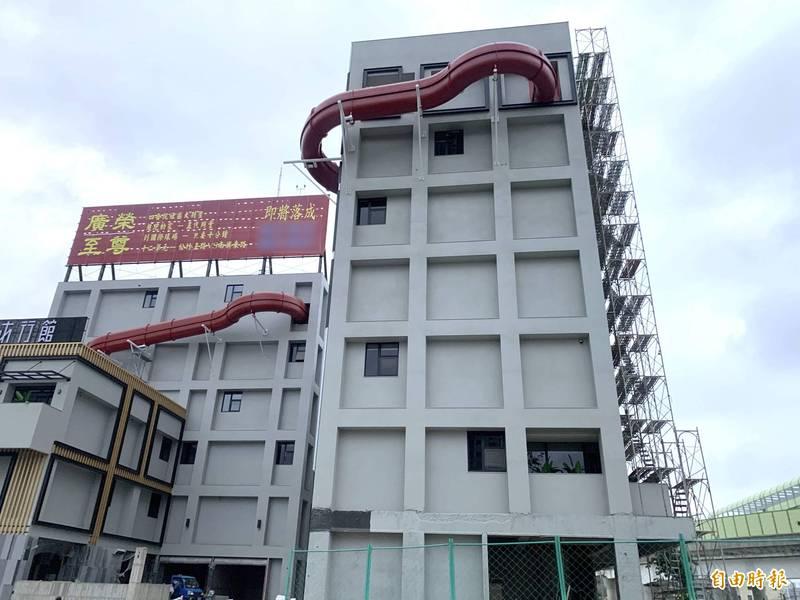 汽車旅館2棟建物外牆分別在7樓及6樓外接紅色的巨大空中滑水道,可以一路滑到下一樓層,引人側目。(記者蔡淑媛攝)