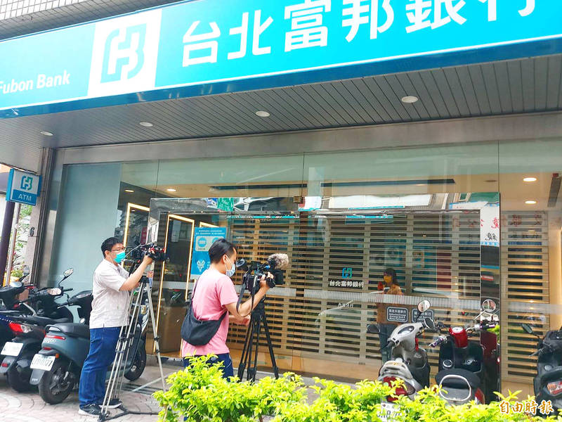 Media workers yesterday set up cameras in front of a Taipei Fubon Commercial Bank branch in Taipei's Neihu District, which was visited by a woman who tested positive for COVID-19. Photo: Yang Hsin-hui, Taipei Times