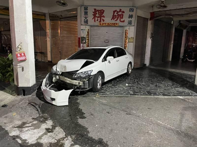 白色轎車失控波及一旁店家,致鐵捲門凹陷毀損,白車駕駛肇事後逃逸,警方在車內發現一批子彈散落在前後腳踏墊、座椅上。(圖由讀者提供)