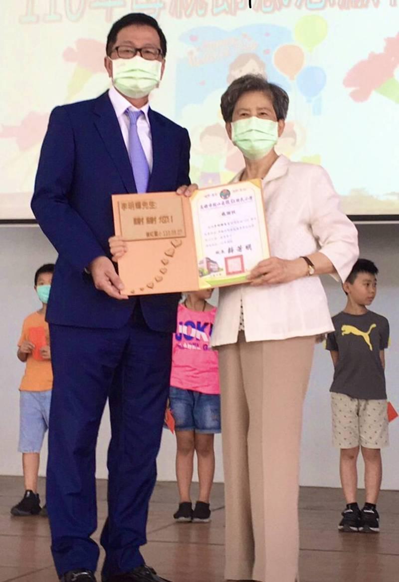 李明輝(左)返回母校頒發獎助學金,當年導師陳瑞柳(右)代表學校致贈感謝狀。(圖教育局提供)
