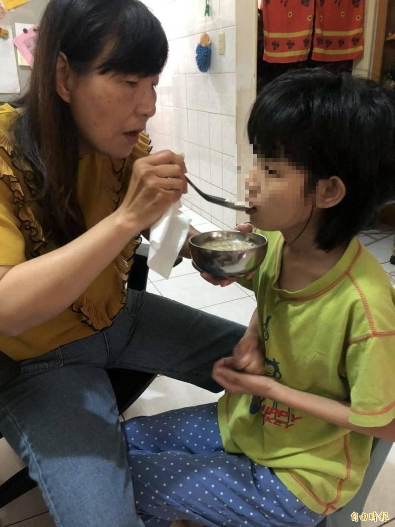 林彩卿(左)幫女兒餵食。(記者陳文嬋攝)