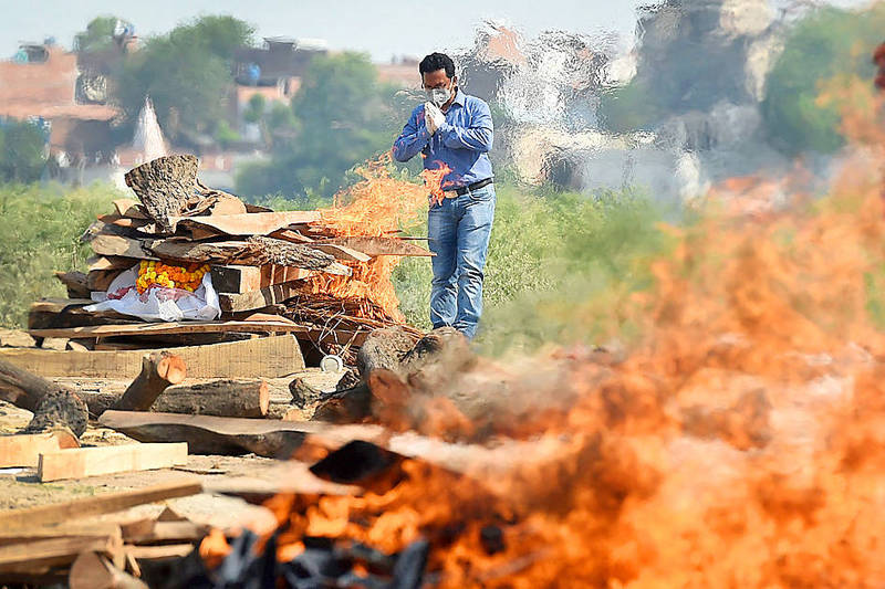 A man offers prayers during the cremation of a relative who died of COVID-19 in Allahabad, India, on Saturday. Photo: AFP