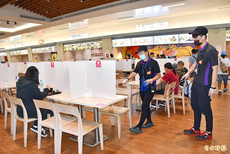 Workers disinfect the food court at the Gloria Outlets shopping mall in Taoyuan yesterday.  Photo: Lee Jung-ping, Taipei Times