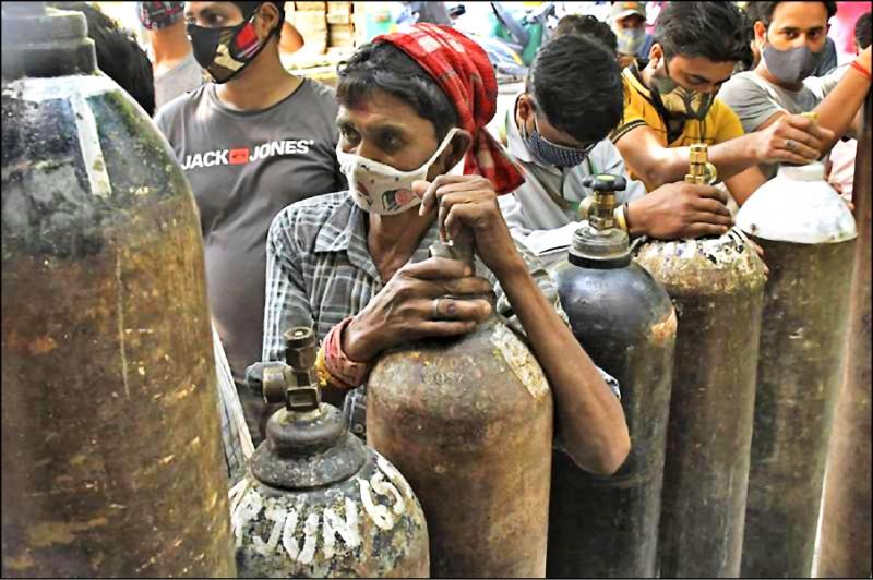印度疫情嚴峻,許多病患因無法入院治療,只能自力救濟吸氧續命,圖為印度民眾排隊等待填充氧氣的畫面。(美聯社)