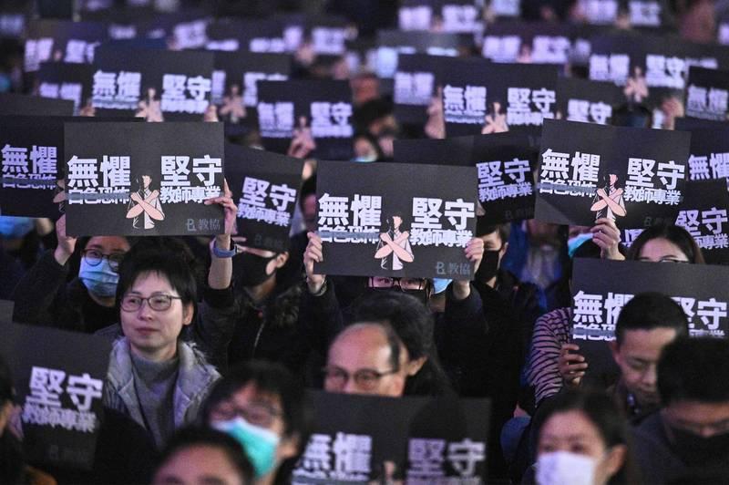 香港教育專業人員協會的問卷調查結果顯示,多達4成的受訪教師有意離開教育界,原因以「政治壓力日增」居冠。圖為去年1月3日,香港教師和民主派支持者在中環愛丁堡廣場集會,主題為「無懼白色恐怖、堅守教師專業」。(法新社檔案照)
