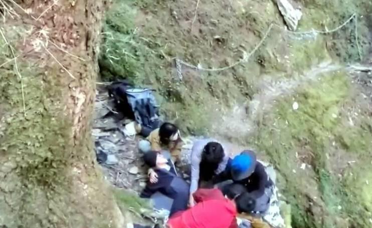 王姓山友在八大秀山域受傷,其同行山友在旁照顧。(南投縣消防局提供)