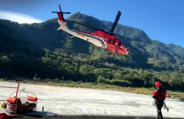 南投縣信義鄉八大秀山域發生登山意外,透過直昇機將傷者吊掛送下山就醫。(南投縣消防局提供)