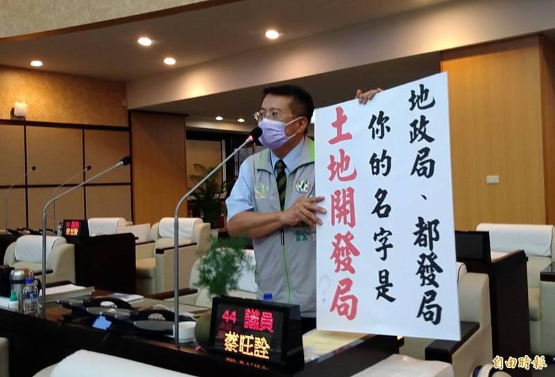 南市議員蔡旺詮出示預做的標語,舉牌質疑「地政局、都發局是『土地開發局』嗎?」(記者蔡文居攝)