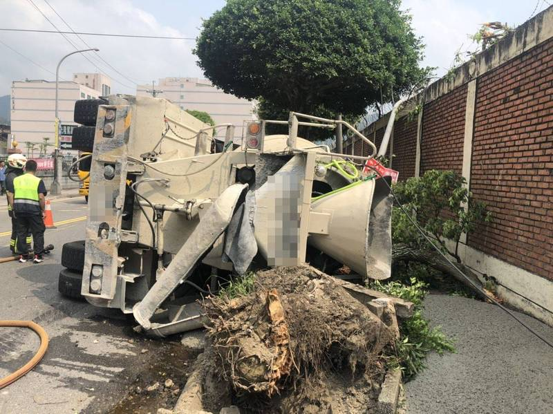 水泥預拌車翻覆後,壓斷路旁行道樹及花圃。(記者吳昇儒翻攝)