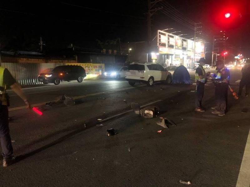 機車零件沿路散落,肇事的白色轎車停在死者(藍色帳篷)旁邊。(記者洪定宏翻攝)