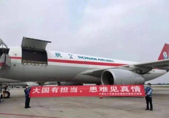中國人員在運送物資的班機旁拉起紅布條寫著「大國有擔當,患難見真情」。(擷取自微博)