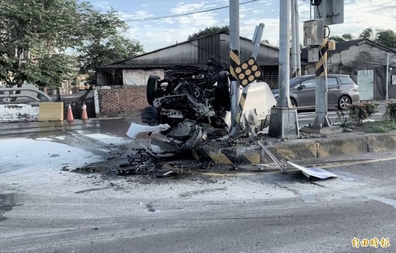 休旅車撞到中央分隔島後車頭全毀。(記者葉永騫攝)
