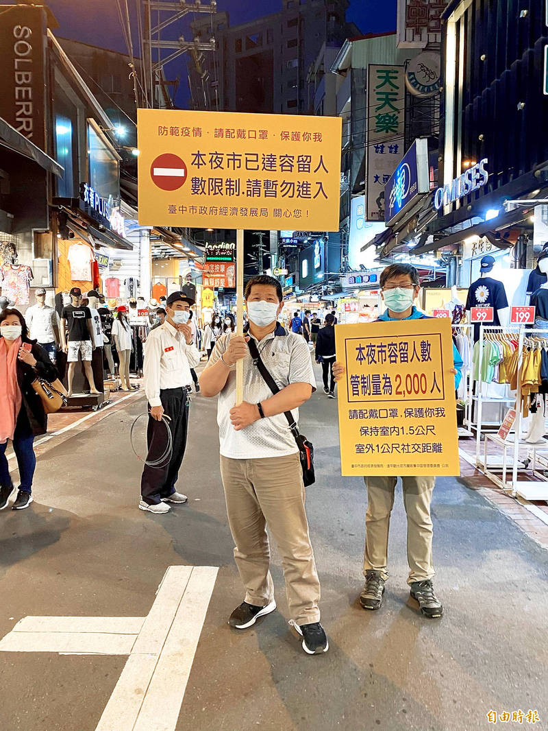Workers at Feng Chia Night Market in Taichung hold signs in an undated photograph. The Central Epidemic Command Center yesterday raised the COVID-19 warning to level 2 and implemented new restrictions and measures effective until June 8, including asking that people practice social distancing at night markets. Photo copied by Tsai Shu-yuan, Taipei Times