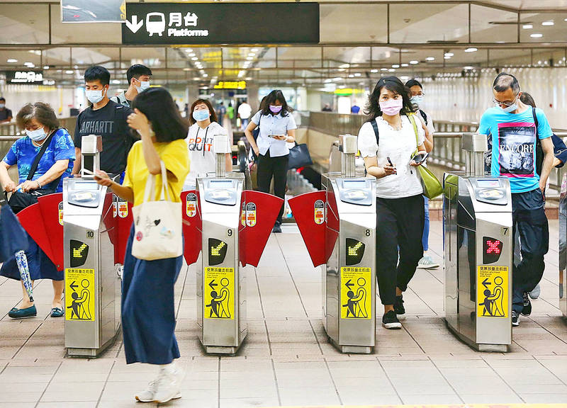 People pass through the gates of an MRT station in Taipei yesterday, as the Ministry of Transportation and Communications urged people to follow the Central Epidemic Command Center's rules when using public transportation. Photo: CNA