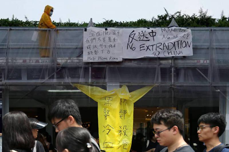 2019年6月15日晚間,穿著黃色雨衣的香港社運人士梁凌杰在金鐘太古廣場高處掛標語,不久後便墜樓身亡,成為首位在反送中運動中犧牲生命的示威者。(本報合成)