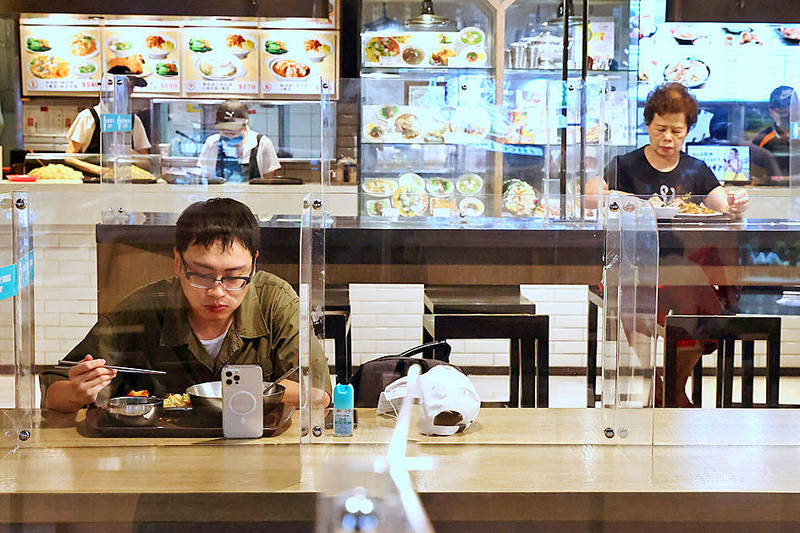 People eat behind plastic partitions at an eatery in Taipei yesterday. Photo: Ann Wang, Reuters