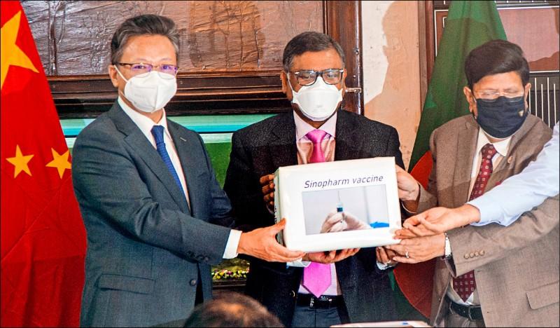 中國捐贈中國國藥(Sinopharm)的武漢肺炎疫苗給孟加拉,駐孟加拉大使李極明(左)十二日在捐贈儀式上,將一批疫苗交給孟加拉衛生部長馬勒克(Zahid Maleque,中)、外交部長摩門(A. K. Abdul Momen,右)。(歐新社)