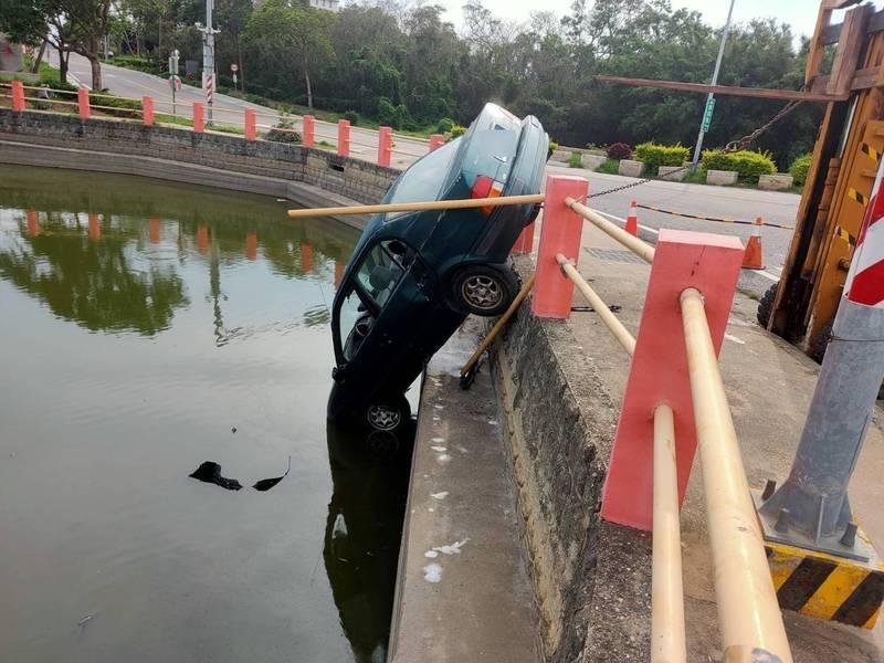 金門一名陳姓男子駕車不慎駛入路旁池塘,一旁工人利用堆高機的鐵鍊,幫忙將車子固定。(讀者提供)