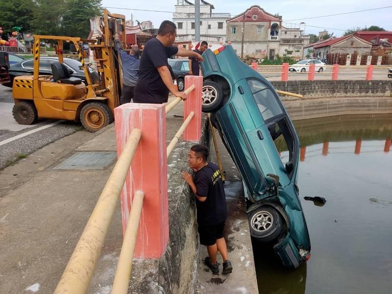 一輛轎車栽入池塘中,幸好池水不深。(讀者提供)