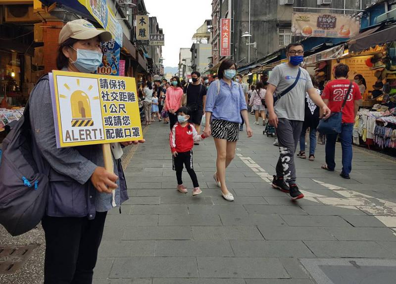 桃園市政府風景區管理處志工在大溪老街提醒民眾配合防疫,保持社交距離或配戴口罩。(記者李容萍翻攝)