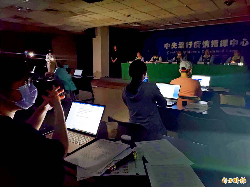 Journalists sit in near darkness amid a power cut at a news conference at the Central Epidemic Command Center in Taipei yesterday. Photo: Wu Liang-yi, Taipei Times