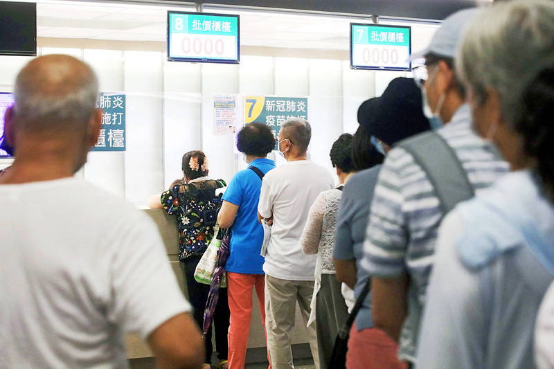 People wait in line at a COVID-19 vaccination center in New Taipei City yesterday. Photo: Cheng I-Hwa, Bloomberg