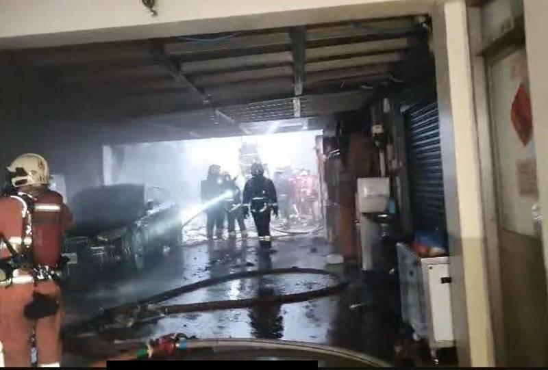 新北市三重光復路二段一間工廠失火,波及後方另間工廠,消防員殘火處理。(記者吳仁捷翻攝)