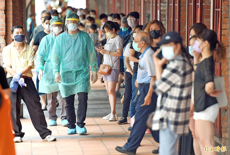 People yesterday line up at a COVID-19 testing site in Taipei's Wanhua District as medical workers arrive to open the station. Photo: Liao Chen-huei, Taipei Times