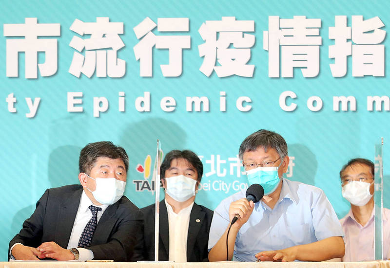 Minister of Health and Welfare Chen Shih-chung, left, listens as Taipei Mayor Ko Wen-je, second right, speaks at a news conference in Taipei yesterday. Photo: CNA