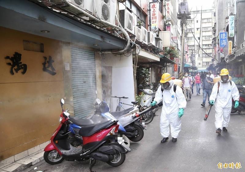 萬華茶館爆群聚感染引發高度關注,網路假消息滿天飛!圖為台北市環保局派員到場消毒。(資料照)