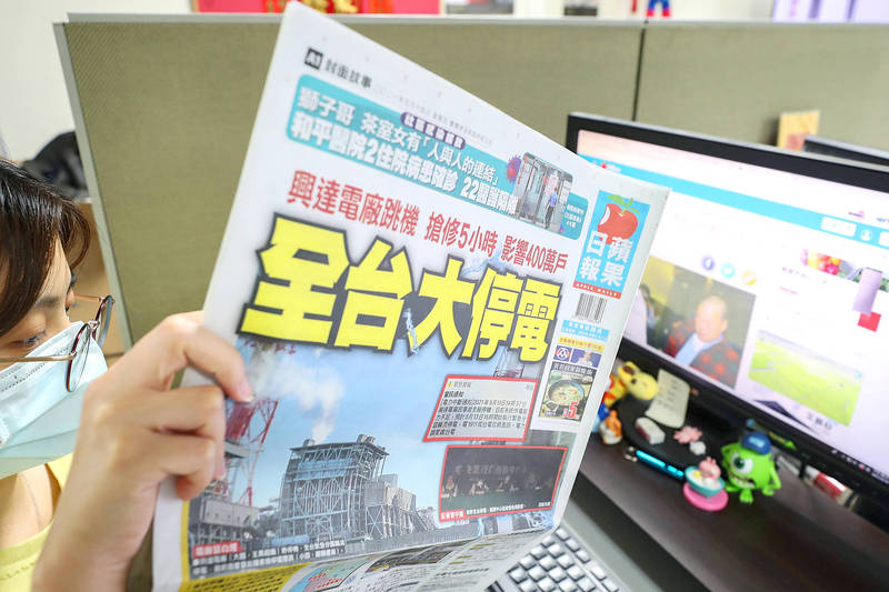A woman reads a copy of the Apple Daily in an office in Taipei yesterday. Photo: CNA
