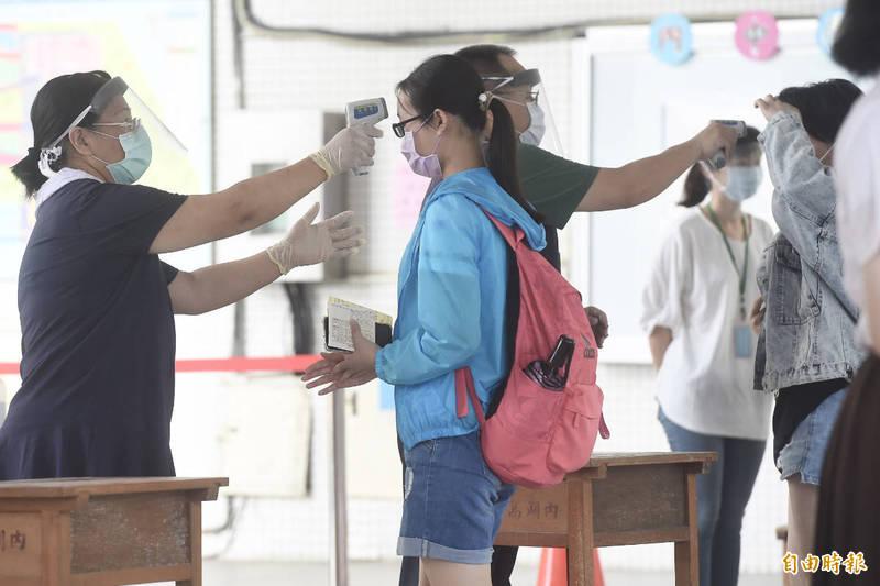 國中會考16日第二天考試,由於疫情升溫,考生須量測體溫、全程佩戴口罩並且不開放陪考,進考場前服務學生及師長幫考生消毒、量體溫。(記者簡榮豐攝)