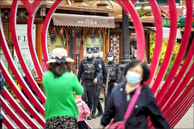 網路流傳一份美國駐中國領事官員通知,美方暫停簽發簽證給中國高官及其妻小。圖為十二日一群警察戴口罩巡邏「新疆國際大巴扎」指標購物中心。(彭博)