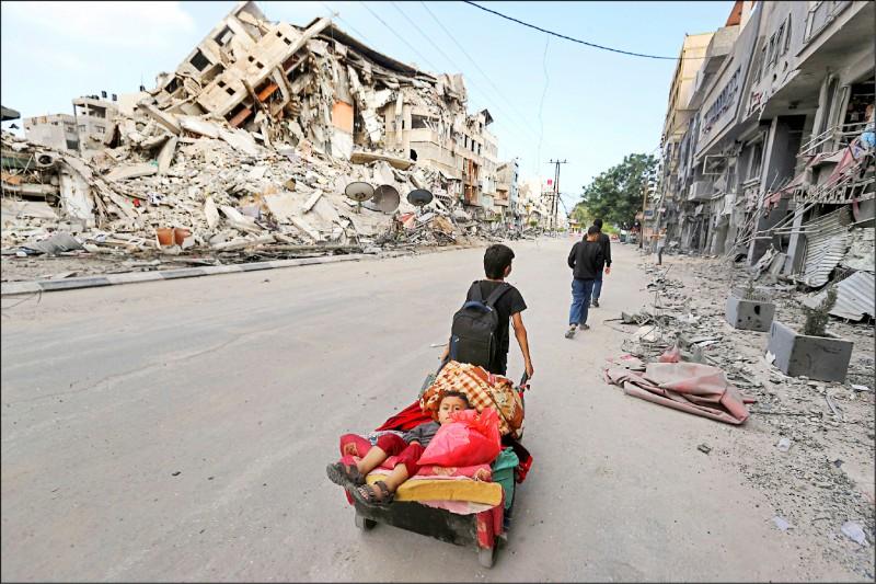一名巴勒斯坦小男孩用推車載著弟弟逃離家園。(路透)
