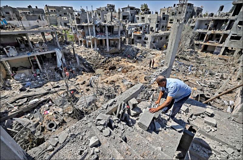 遭以色列強烈轟炸一夜後,加薩北部貝特漢諾鎮民眾十四日檢視房屋殘骸。(法新社)