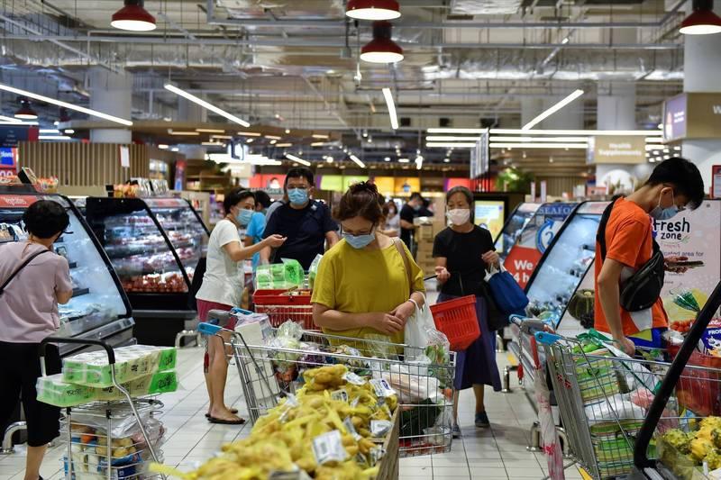新加坡宣布加強防疫措施後,超市賣場湧現採買民生物資的人潮。(路透)