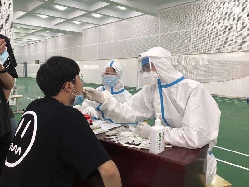 中國再度爆發本土疫情,安徽省六安市1間國中內,穿著防護裝備的醫護人員正在幫學生採檢。(美聯社)