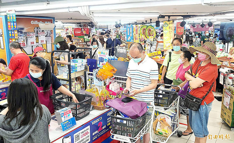 Shoppers yesterday line up at a cashier in a Taipei supermarket packed with people. Photo: Fang Pin-chao, Taipei Times