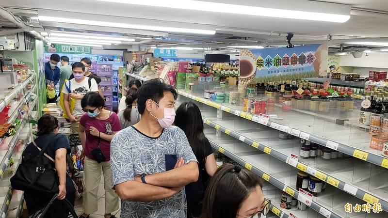 行政院15日召開記者會,宣布台北市和新北市升級為三級防疫警戒,消息一傳出,大型賣場湧入民眾搶購物資。(記者方賓照攝)