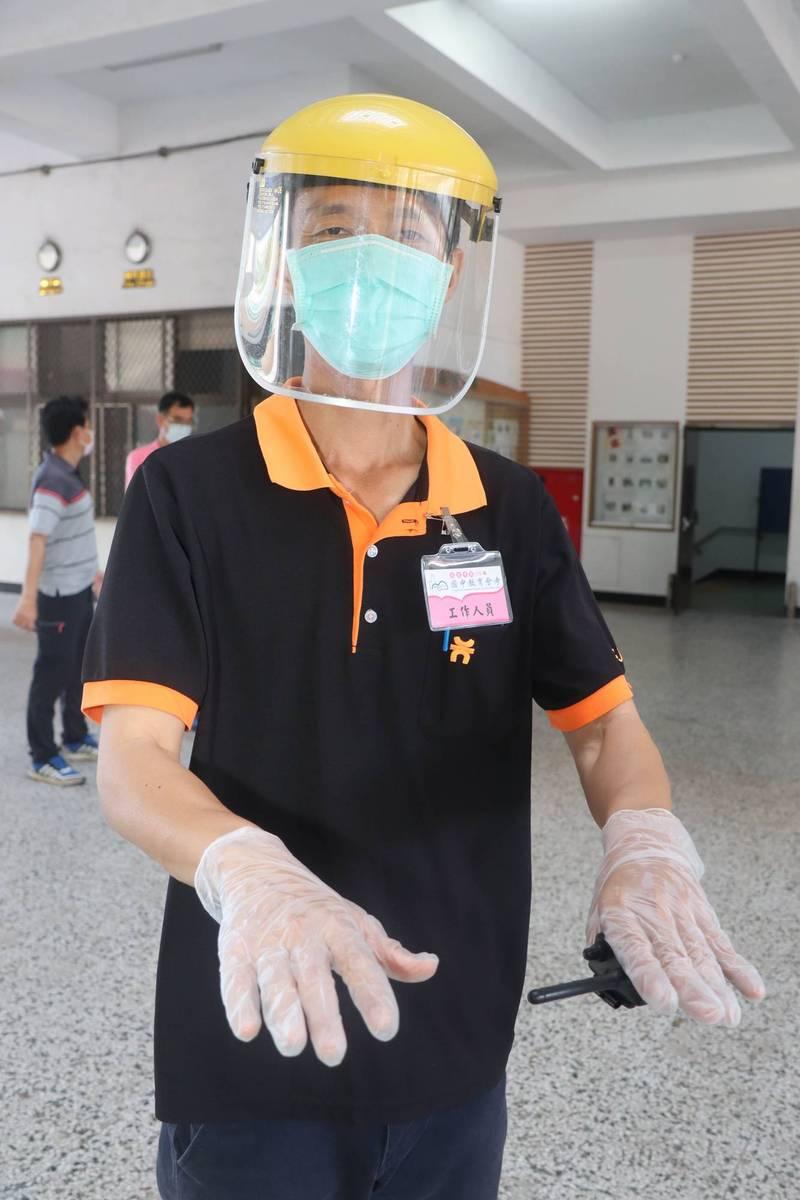 國中會考第二天,各考場入口處,安排有量測體溫人員,均配有防疫頭罩、著手套。(教育局提供)