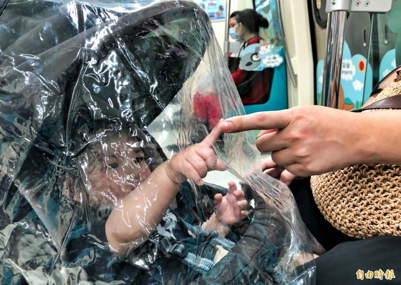 疫情急速升溫,一位媽媽16日推著九個月大男嬰搭乘台北捷運,媽媽隔著嬰兒車外透明塑膠套逗弄兒子,試圖安撫。(記者羅沛德攝)