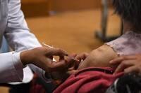 日本沖繩近日發生有醫護人員僅給民眾施打生理食鹽水的烏龍事件。圖為日本民眾接種武肺疫苗示意圖,與本文無關。(彭博)