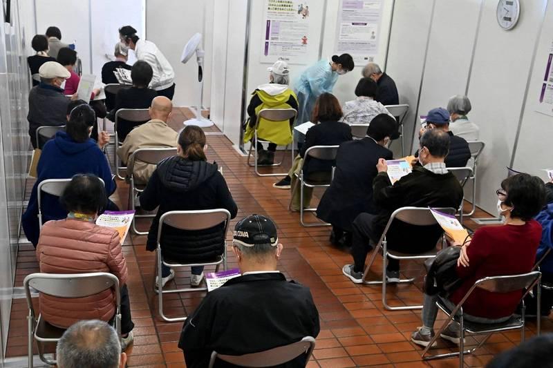 日本1名80來歲老婦注射武漢肺炎疫苗後,坐在旁邊等待觀察時間過去,孰料又被打了1劑疫苗。日本接種疫苗示意圖。(法新社)