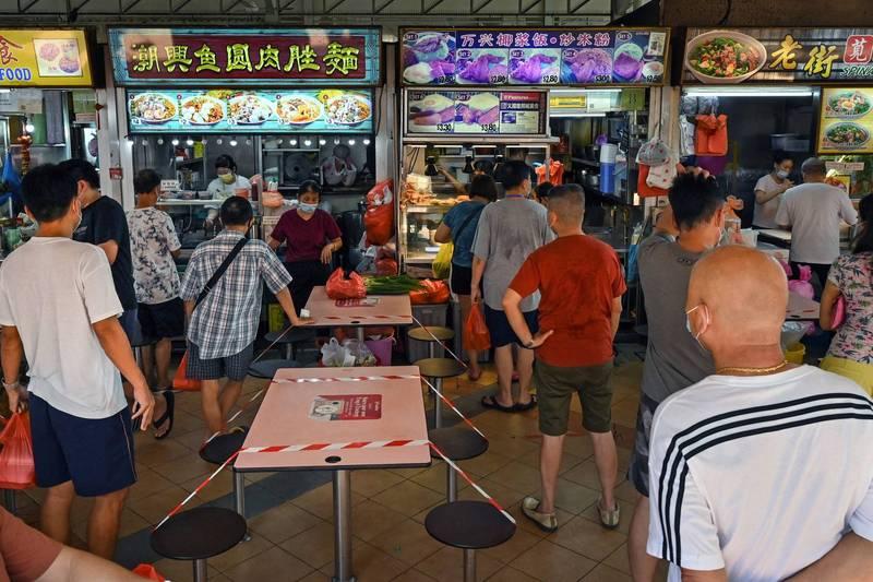 新加坡昨提升防疫限制,美食街的用餐桌椅都貼上封鎖條。(法新社)