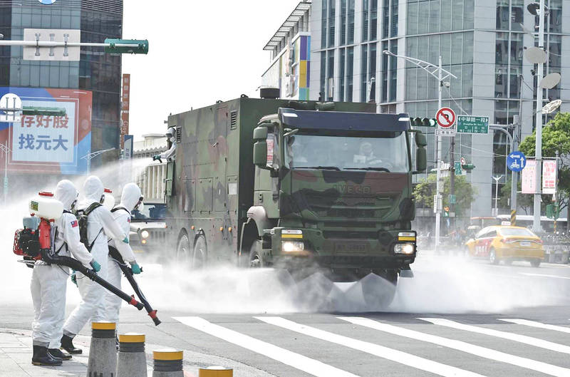 A truck sprays disinfectant along a street in Taipei's Wanhua District yesterday as health officials attempt to suppress an outbreak of COVID-19 cases in the area. Photo: CNA / Military News Agency