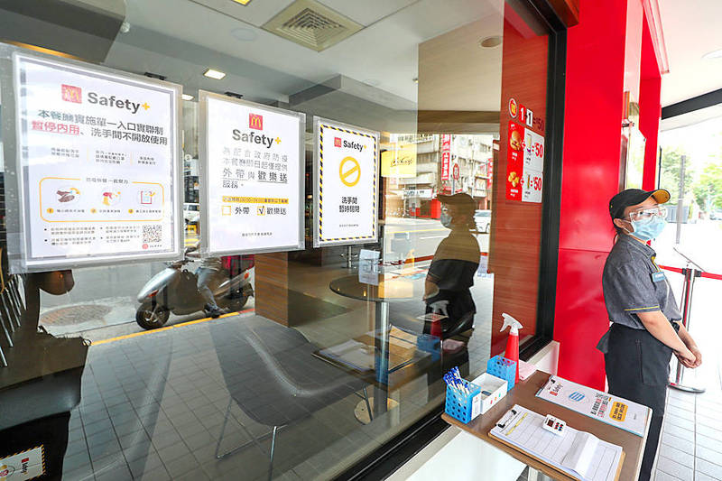 An employee at a McDonald's restaurant in Taipei yesterday stands next to signs saying the store had suspended dine-in services until Friday next week. Photo: CNA